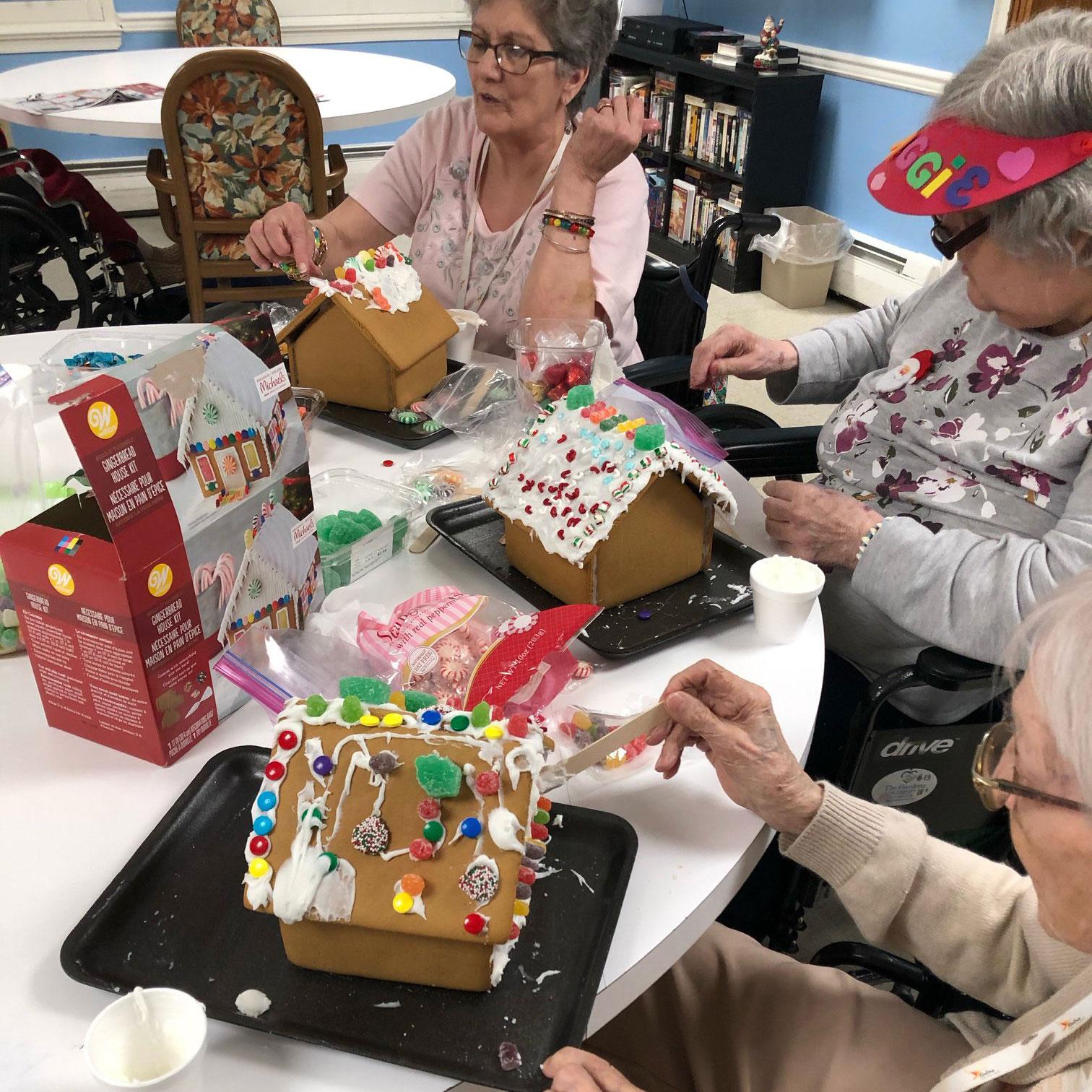 Image of women making gingerbread houses at Kadima at Pottstown Nursing and Rehabilitation Facility