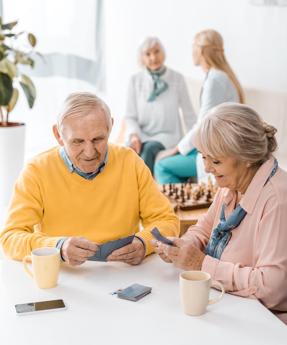photo of Elderly Couple Playing Cards and Kadima Nursing Home Facility
